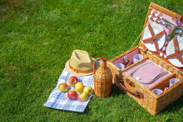 Canestro da picnic su prato inglese soleggiato verde nel parco