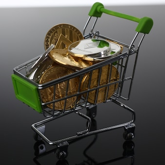 Canestro dal supermercato con il litetcoin ethereum del bitcoin di valuta e del cripto di monete su un fondo grigio nero con il primo piano dello scambiatore di vendita di acquisto di scambio di riflessione.