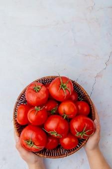 Canestro della tenuta della donna dei pomodori su superficie bianca