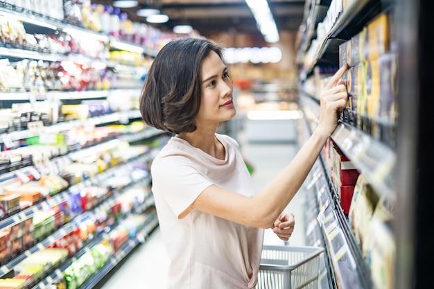 Canestro di drogheria della giovane bella donna asiatica della tenuta che cammina nel supermercato, guardante e scegliendo le cose da comprare con il sorriso.