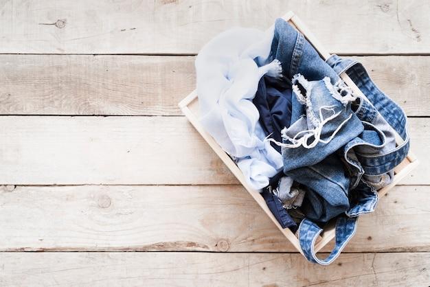 Canestro di lavanderia pieno di vista superiore con fondo di legno