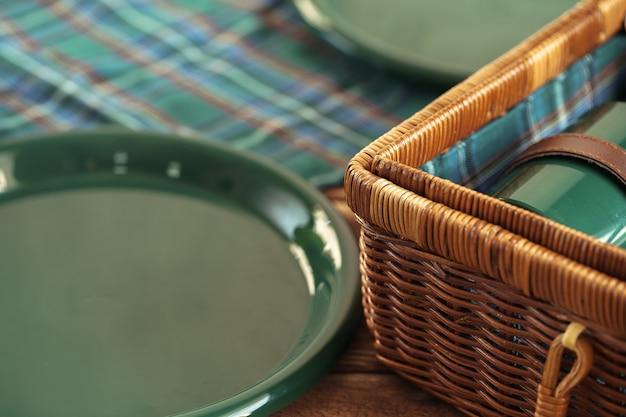 Canestro di legno per il picnic con alto vicino dei piatti, delle tazze e dell'argenteria