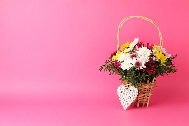 Canestro di vimini con i fiori e cuore sul rosa