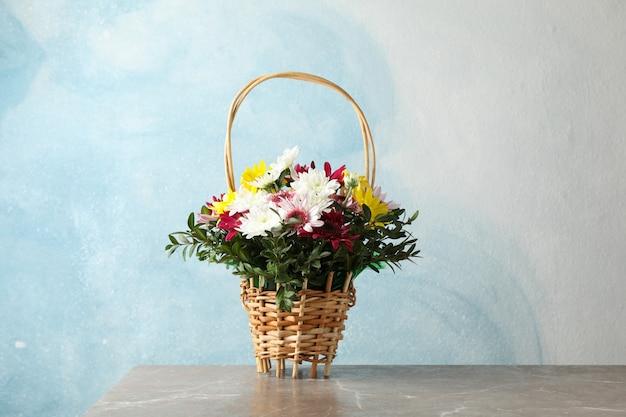Canestro di vimini con i fiori sulla tavola grigia contro il blu