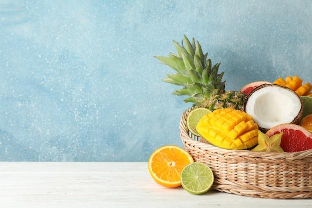 Canestro di vimini con i frutti esotici su fondo di legno bianco, spazio per testo
