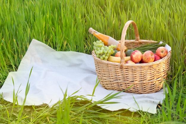 Canestro di vimini di picnic con alimento su erba nel campo