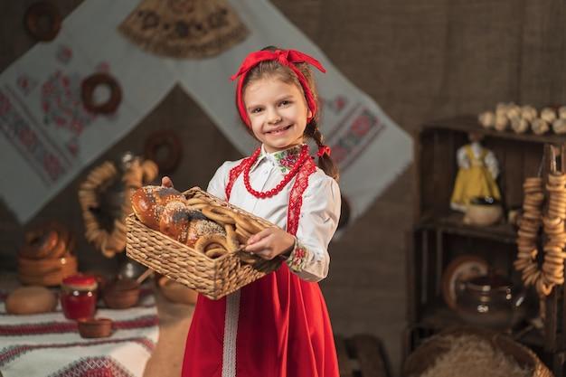 Canestro grazioso della tenuta della ragazza dei bagel e dell'altra cottura nella casa tradizionale che celebra maslenitsa