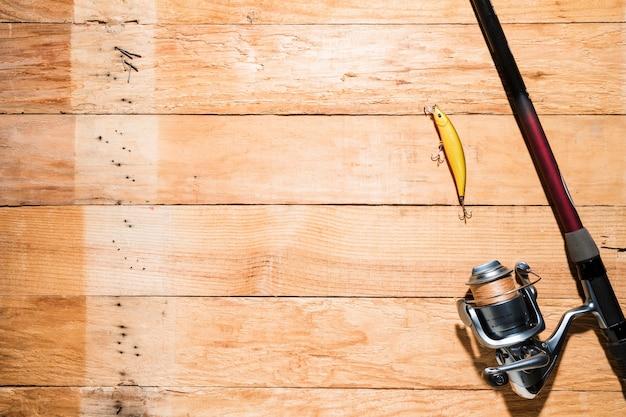Canna da pesca con esche da pesca gialla sulla tavola di legno