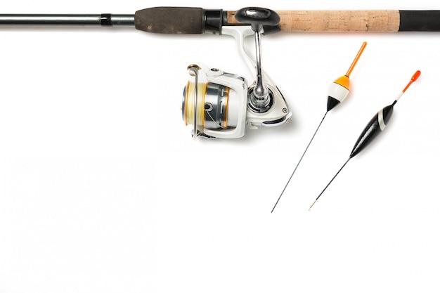 Canna da pesca con la bobina e le boe di pesca isolate su bianco