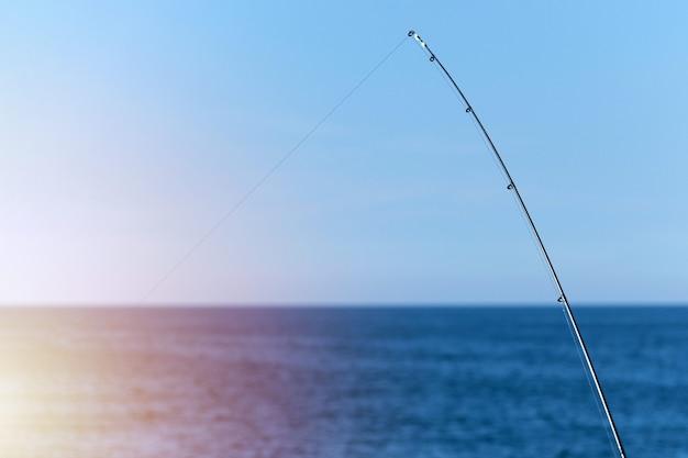 Canna da pesca contro il fondo blu del mare o dell'oceano