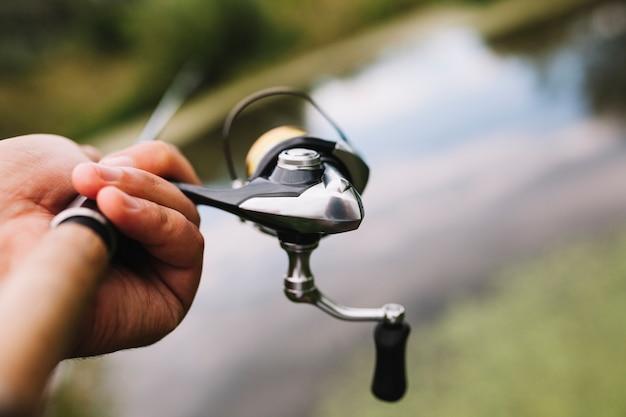 Canna da pesca della holding della mano del pescatore