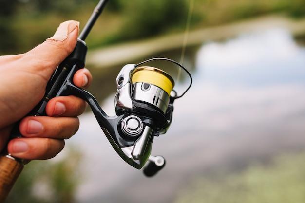 Canna da pesca della tenuta del pescatore sul fondo della sfuocatura