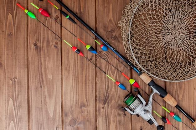 Canna da pesca galleggiante da pesca e esche sul bellissimo legno blu