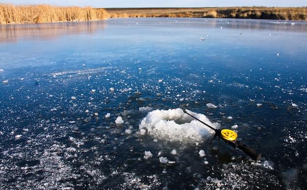 Canna da pesca invernale sdraiato sul ghiaccio vicino al buco