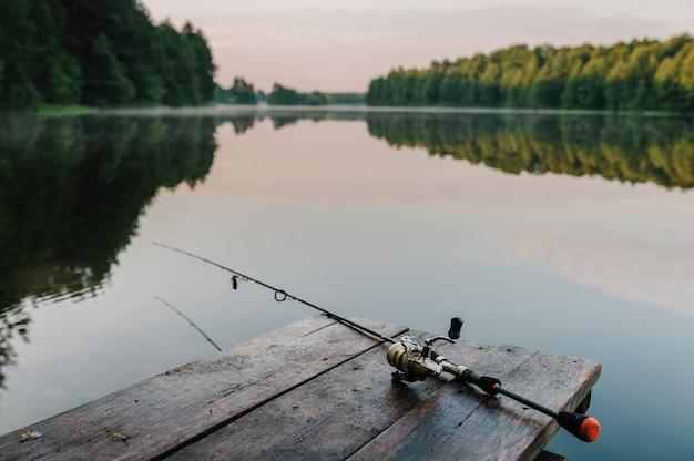 Canna da pesca, mulinello da spinning. nebbia sullo sfondo del lago. articolo sulla giornata di pesca.