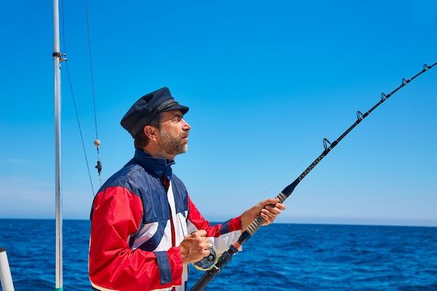 Canna da pesca uomo barba marinaio trolling in acqua salata