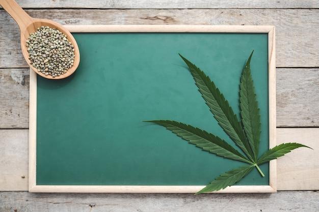 Cannabis, semi di cannabis, foglie di cannabis, disposte su una tavola verde su un pavimento di legno.