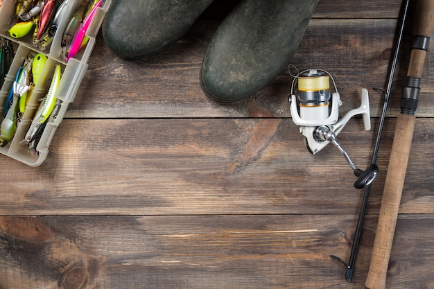 Canne da pesca e bobina con gli stivali e le attrezzature da pesca in una scatola su fondo di legno