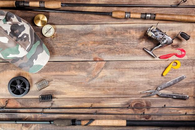 Canne da pesca e mulinello con cappuccio, attrezzatura da pesca, linea e bussola su legno
