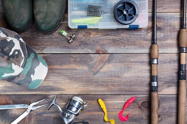 Canne da pesca e mulinello con stivali, berretto e attrezzi da pesca in una scatola su legno