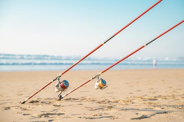 Canne da pesca sulla spiaggia sabbiosa del mare in un giorno soleggiato di estate