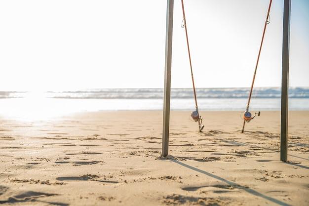 Canne da pesca sulla spiaggia sabbiosa dell'oceano in una soleggiata giornata estiva