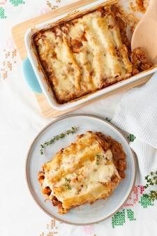 Cannelloni con ripieno di carne macinata di manzo, pomodori, al forno con salsa di pomodoro besciamella