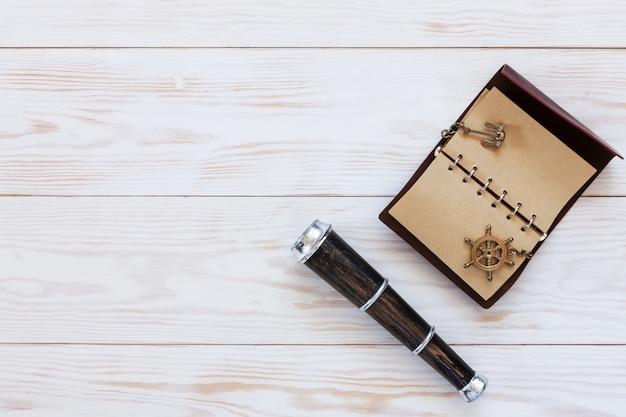 Cannocchiale, un quaderno con un'ancora e un volante. sfondo accessori mare