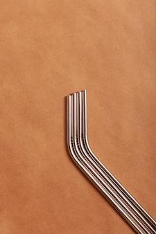 Cannucce da cocktail ecologiche in metallo su uno sfondo di carta artigianale. vista dall'alto