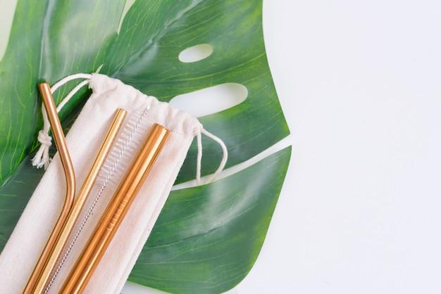 Cannucce da cocktail in metallo, una spazzola per la pulizia dei tubi e una borsa ecologica su una foglia di monstera, il concetto di zero rifiuti e uno stile di vita ecologico
