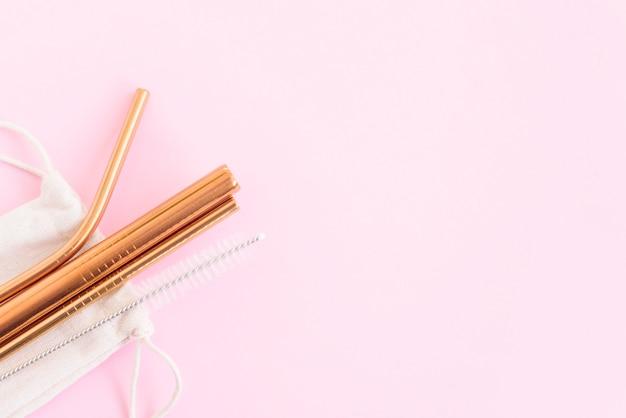 Cannucce da cocktail in metallo, una spazzola per la pulizia dei tubi e una borsa ecologica su uno sfondo rosa, il concetto di zero rifiuti e uno stile di vita ecologico