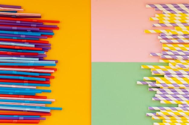 Cannucce di carta vs cannucce di plastica su colorati wall.colored tubules per succo e cocktail. forniture per eventi e feste.