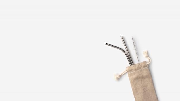 Cannucce ecologiche in acciaio inossidabile in una custodia di lino su uno sfondo bianco