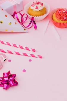 Cannucce; fiocco di nastro; cappello da festa; filanti; pacco regalo; cupcake e candele su sfondo rosa