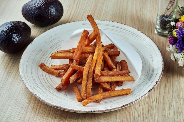 Cannucce fritte nel grasso bollente della patata dolce sul piatto grigio. visualizza. cibo vegetariano. cibo di strada