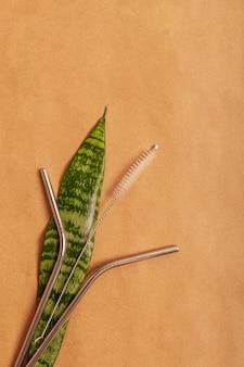 Cannuccia riutilizzabile del cocktail del metallo su un foglio verde su un fondo della carta del mestiere. vista dall'alto