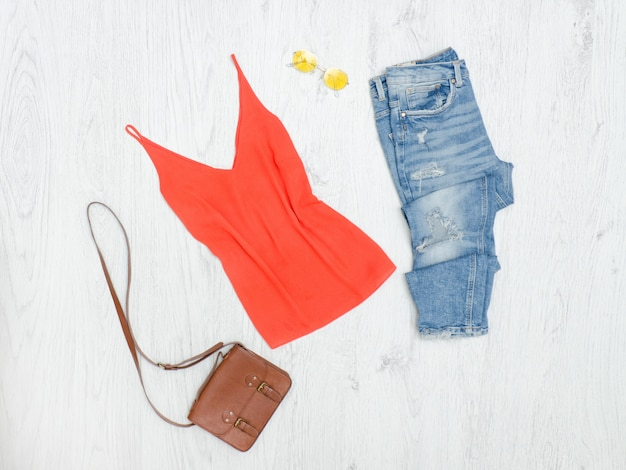 Canotta arancione, jeans strappati, borsa e occhiali da sole. concetto alla moda