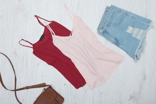 Canotta rosa e bordeaux, pantaloncini di jeans strappati. concetto alla moda