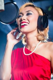 Cantante asiatico che produce canzone in studio di registrazione
