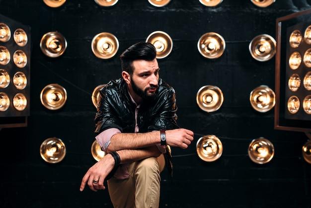 Cantante barbuto in giacca di pelle nera sul palco con decorazioni di luci
