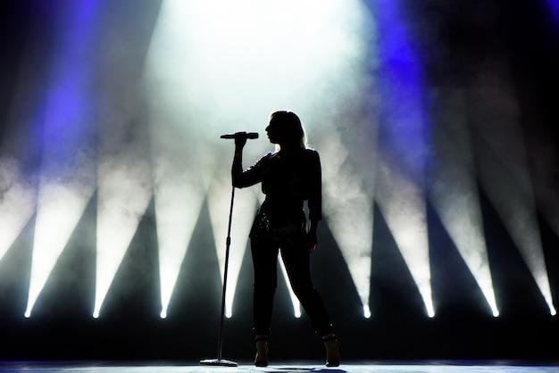 Cantante che canta al microfono. cantante in silhouette