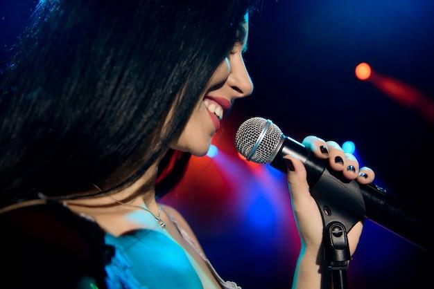 Cantante con microfono sullo sfondo colorato palcoscenico leggero