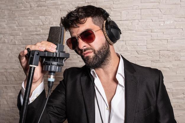 Cantante con occhiali da sole davanti a un microfono che lo tiene a mano e con alcuni elmetti