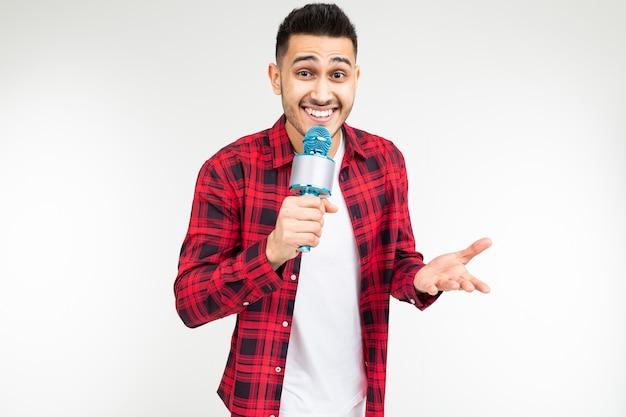 Cantante del tipo di esecutore in una camicia con un microfono in sue mani su una priorità bassa bianca