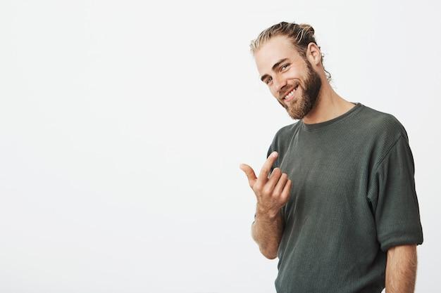Cantante famoso attraente che chiama con un dito e che sorride delicatamente