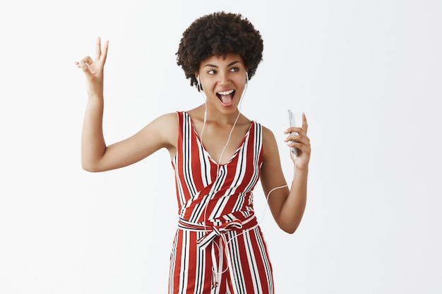 Cantante femminile attraente e spensierata dalla pelle scura con acconciatura afro, ascolto di musica in cuffia, che mostra il segno di pace o di vittoria, sporge la lingua e tiene il telefono