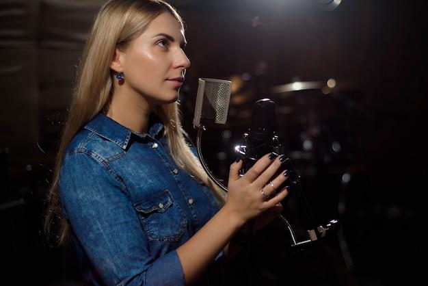 Cantante femminile che canta una canzone. donna che si esibisce in uno studio di registrazione