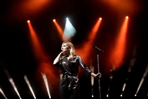 Cantante in scena nel club. illuminazione scenica brillante.