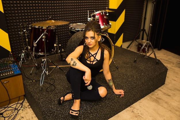 Cantante rock che registra il suono in studio professionale con microfono sulla parete a strisce