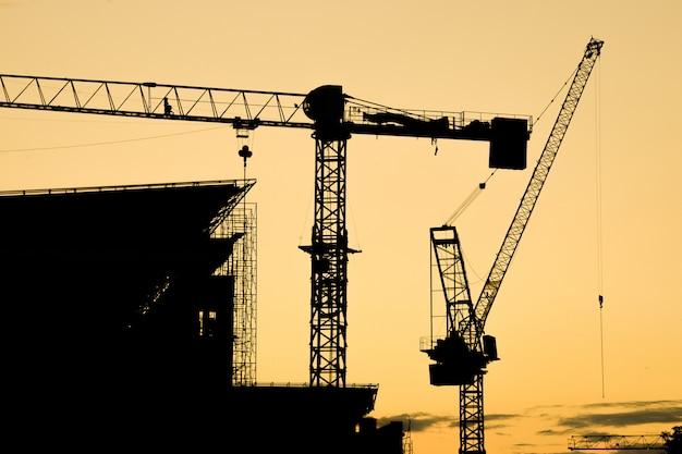 Cantiere con la gru al tramonto siluetta del gruppo della gru a torre della costruzione con il cielo di tramonto